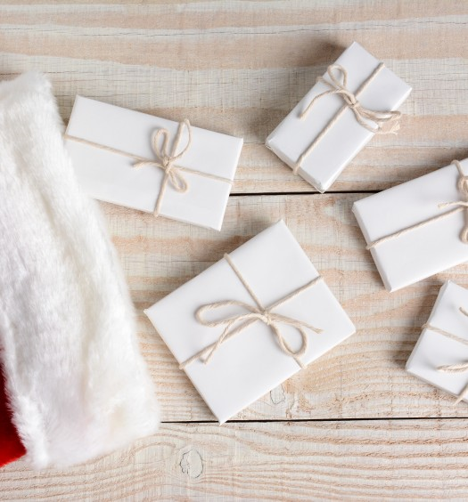 High angle photo of five Christmas presents wrapped in white paper and tied with white string and a stocking. The gifts are on a whitewashed wood table. Horizontal format.